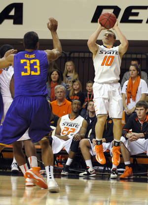 photo - Oklahoma State guard Phil Forte, right, shoots over Tennessee Tech forward Dennis Ogbe, left, during the second half of an NCAA college basketball game in Stillwater, Okla., Saturday, Dec. 22, 2012. Forte scored 22 points in the 78-42 win over Tennessee Tech. (AP Photo/Brody Schmidt) ORG XMIT: OKBS105