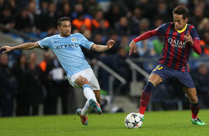 Photo - Barcelona's Neymar fights for the ball Manchester City's Gael Clichy, left, during their Champions League first knock out round soccer match at the Etihad Stadium, Manchester, England, Tuesday Feb. 18, 2014. (AP Photo/Jon Super)