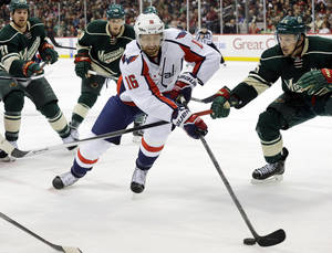 Photo - Washington Capitals right wing Eric Fehr (16) controls the puck past Minnesota Wild defenseman Jonas Brodin, right, during the second period of an NHL hockey game in St. Paul, Minn., Saturday, Jan. 4, 2014. (AP Photo/Ann Heisenfelt)