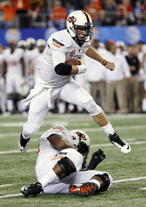 Photo - Oklahoma State's Clint Chelf (10) leaps over a teammate during the AT&T Cotton Bowl Classic college football game between the Oklahoma State University Cowboys (OSU) and the University of Missouri Tigers at AT&T Stadium in Arlington, Texas, Friday, Jan. 3, 2014. Photo by Nate Billings, The Oklahoman