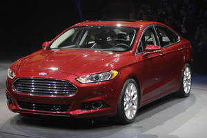photo -   FILE - In this Jan. 9, 2012 file photo, the 2013 Ford Fusion is introduced during the North American International Auto Show in Detroit. Ford hopes the redesigned 2013 Fusion will finally be its Camry killer. The Fusion has become Ford's best-selling car since it went on sale in 2005, and it's one of the top sellers in the country. But Ford hopes the sexier styling, improved fuel economy and cool features like automatic parallel parking on the new Fusion will help it finally trounce the perennial leader, the Toyota Camry. (AP Photo/Carlos Osorio)