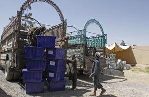 Photo - Afghan election workers load ballot boxes and election materials into trucks to deliver to polling stations, at a warehouse in Kandahar, Afghanistan, Thursday, June 12, 2014. The second round of Afghanistan's presidential election will take place on June 14, 2014. (AP Photo/Allauddin Khan)