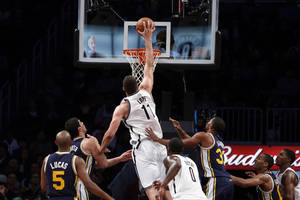 Photo - Brooklyn Nets' Brook Lopez (11) dunks against against the Utah Jazz during the first half of an NBA basketball game Tuesday, Nov. 5, 2013, in New York. (AP Photo/Jason DeCrow)