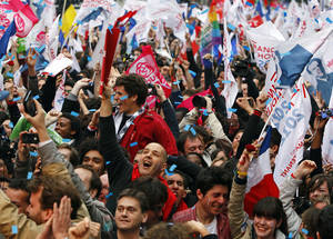 Photo -   Supporters of Socialist Party candidate for the presidential election Francois Hollande react after the first results of the second round of French presidential elections outside Socialist Party campaign headquarters in Paris, France, Sunday, May 6, 2012. First results show that Hollande had won the election. (AP Photo/Francois Mori)