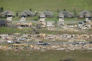 Photo - A row of lightly damages houses, top, face destroyed homes in a Vilonia, Ark., neighborhood Monday, April 28, 2014 after a tornado struck the town late Sunday, killing at least 16 people.   (AP Photo/Danny Johnston)