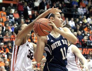 Photo - Notre Dame forward Natalie Achonwa, right, looks for an outlet pass under the basket as Oregon State forward Deven Hunter defends during the first half of an NCAA college basketball game in Corvallis, Ore., Sunday, Dec. 29, 2013. (AP Photo/Don Ryan)