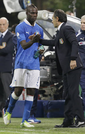 photo -   Italy coach Cesare Prandelli congratulates forward Mario Balotelli during a World Cup Group B qualifying soccer match between Italy and Denmark, in Milan, Italy, Tuesday, Oct.16, 2012. (AP Photo/Luca Bruno)