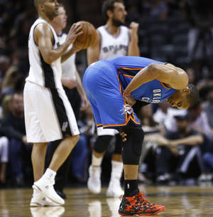 Photo - Oklahoma City's Russell Westbrook (0) reaches for his knee during Game 2 of the Western Conference Finals in the NBA playoffs between the Oklahoma City Thunder and the San Antonio Spurs at the AT&T Center in San Antonio, Wednesday, May 21, 2014. Photo by Sarah Phipps, The Oklahoman