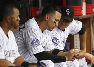 Photo - Colorado Rockies left fielder Carlos Gonzalez, center, shows his fingers to bench coach Tom Runnells, right, while facing the Miami Marlins in the third inning of a baseball game in Denver, Thursday, July 25, 2013. Gonzalezplayed in the fourth inning but was removed from the game upon returning to the dugout. (AP Photo/David Zalubowski)