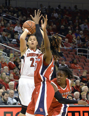 Photo - Louisville's Shoni Schimmel, left, puts up a shot over Houston's Yasmeen Thompson, center, and Alecia Smith during the first half of an NCAA college basketball game Wednesday, Feb. 19, 2014, in Louisville, Ky. Schimmel scored 15 points to become the second player to score over 2000 points in Louisville history. (AP Photo/Timothy D. Easley)