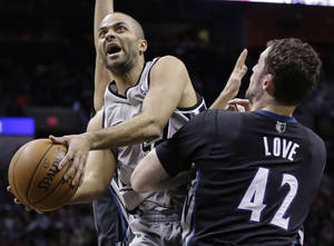 Photo - San Antonio Spurs' Tony Parker, left, of France, shoots over Minnesota Timberwolves' Kevin Love (42) during the first half of an NBA basketball game, Sunday, Jan. 12, 2014, in San Antonio.  (AP Photo/Eric Gay)