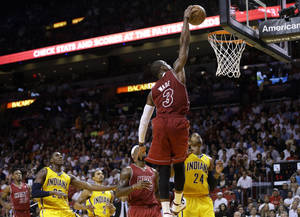 Photo - Miami Heat's Dwyane Wade (3) dunks over Indiana Pacers' Ian Mahinmi, left, and Paul George (24) during the second half of an NBA basketball game, Wednesday, Dec. 18, 2013, in Miami. The Heat defeated the Pacers 97-94. (AP Photo/Lynne Sladky)