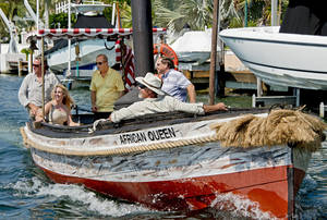 photo - In this April 12, 2012, photo provided by the Florida Keys News Bureau, the African Queen, the original vessel from the classic 1951 movie by the same name, sails on a Key Largo, Fla., canal steered by Stephen Bogart, center, son of Humphrey Bogart, who starred in the film. Stephen Bogart is to host the Bogart Film Festival, set for May 2-5, 2013, in Key Largo. Built in 1912, the 30-foot boat was refurbished to provide Florida Keys visitors an opportunity to ride the cinema icon. (AP Photo/Florida Keys News Bureau, Andy Newman)