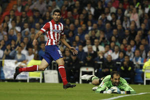 Photo - Atletico de Madrid's Diego Costa from Brazil, left, celebrates his goal after facing Real MAdrid's Diego Lopez during a Spanish La Liga soccer match at the Santiago Bernabeu stadium in Madrid, Spain, Saturday, Sept. 28, 2013. (AP Photo/Andres Kudacki)
