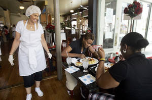 Photo - In this Saturday, July 28, 2007, file photo, Robbie Montgomery, left, talks to diners Tasha Davis, center, and Sylvona Harvey, right, in Sweetie Pie's, Montgomery's soul food restaurant. Turning small business owners into stars has become a winning formula for television producers, but some businesses featured in them are cashing in, too. Sales explode after just a few episodes air, transforming these nearly unknown small businesses into household names. (AP Photo/Jeff Roberson) ORG XMIT: NYBZ308