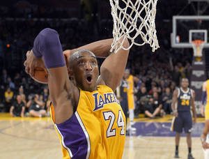 photo - Los Angeles Lakers guard Kobe Bryant goes up for a dunk during the first half of an NBA basketball game against the Utah Jazz, Friday, Jan. 25, 2013, in Los Angeles.  (AP Photo/Mark J. Terrill)