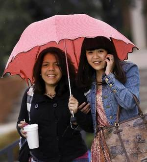 Photo - Vanessa Klie, left, and Yueru Jin, students at Oklahoma Christian University, share an umbrella as light right falls while the pair walks across campus to a parking lot Thursday around noon, Sept. 27, 2012. Photo by Jim Beckel