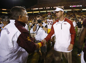 Photo - In this Sept. 28, 2013 photo, Arizona State University head coach Todd Graham, left,  shakes hands with USC head coach Lane Kiffin after ASU defeated USC 62-41 at Sun Devil Stadium in Tempe, Ariz. USC fired Kiffin early Sunday morning, not long after the team lost 62-41 at Arizona State.  (AP Photo/The Arizona Republic, Rob Schumacher) MARICOPA COUNTY OUT. NO SALES