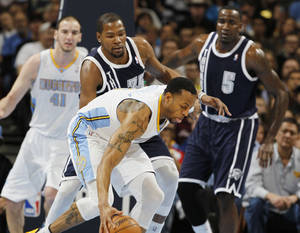 photo - Denver Nuggets guard Andre Iguodala, front, picks up the loose ball as Oklahoma City Thunder forward Kevin Durant, center, covers in the first quarter of an NBA basketball game in Denver on Friday, March 1, 2013. Nuggets center Kosta Koufos, back left, and Thunder center Kendrick Perkins look on. (AP Photo/David Zalubowski) ORG XMIT: CODZ102