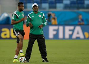 Photo - Nigeria coach Stephen Keshi, right, speaks with his player Mikel John Obi during a training session at the Arena Pantanal in Cuiaba, Brazil, Friday, June 20, 2014. Nigeria plays in group F of the 2014 soccer World Cup. (AP Photo/Fernando Llano)