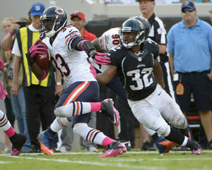 Photo -   Chicago Bears cornerback Charles Tillman (33) runs past Jacksonville Jaguars running back Maurice Jones-Drew (32) after intercepting a pass for a 36-yard touchdown during the second half of an NFL football game, Sunday, Oct. 7, 2012, in Jacksonville, Fla. (AP Photo/Phelan M. Ebenhack)