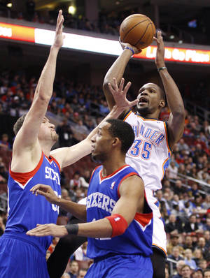 Photo - The Thunder's Kevin Durant shoots as the Sixers' Spencer Hawes, left, and Evan Turner defend during Saturday night's matchup.  AP Photo