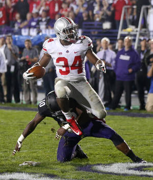 Photo - Ohio State running back Carlos Hyde (34) scores over Northwestern safety Traveon Henry during the second half of an NCAA football game Saturday, Oct. 5, 2013, in Evanston, Ill. Ohio State won 40-30. (AP Photo/Charles Rex Arbogast)