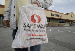 Photo - FILE - In this Feb. 23, 2011 file photo, a customer leaves a Safeway store in Cupertino, Calif. Safeway reports quarterly earnings on Wednesday, April 23, 2014. (AP Photo/Paul Sakuma)