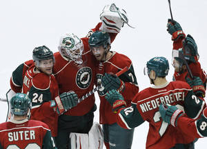 Photo - Minnesota Wild goalie Ilya Bryzgalov, of Russia, celebrates with teammates Matt Cooke (24), Jonathon Blum (7), Nino Niederreiter (22), of Switzerland, and others after the Wild defeated the Boston Bruins 4-3 during a shootout in an NHL hockey game in St. Paul, Minn., Tuesday, April 8, 2014.  (AP Photo/Ann Heisenfelt)