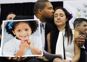 Photo - Jimmy Greene, left, kisses his wife Nelba Marquez-Greene as he holds a portrait of their daughter, Sandy Hook School shooting victim Ana  Marquez-Greene at a news conference at Edmond Town Hall in Newtown, Conn., Monday, Jan. 14, 2013. One month after the mass school shooting at Sandy Hook Elementary School, the parents joined a grassroots initiative called Sandy Hook Promise to support solutions for a safer community. (AP Photo/Jessica Hill)