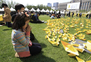 Photo - A girl prays in front of paper ships bearing messages for the victims of the sunken ferry Sewol at a group memorial altar in Seoul, South Korea, Monday, May 5, 2014. More than 300 people are dead or missing in the water off the southern coast in the disaster that caused widespread grief, anger and shame. (AP Photo/Ahn Young-joon)