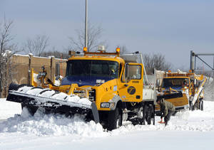 Photo - A New York State Department of Transportation plow is dug out of the snow after being stuck near Exit 60 eastbound on the Long Island Expressway after a storm, Saturday, Feb. 9, 2013, in Ronkonkoma, N.Y. (AP Photo/Kathy Kmonicek)