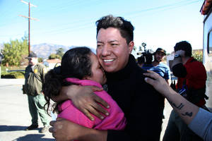 Photo - Alex Montero hugs his wife Paola Montero after he and three other mountain bikers were found safe by search and rescue teams, after spending a night in the chilly Angeles National Forest near Pasadena, Calif., on Monday, Dec. 23, 2013. The men began their ride from a towering peak in the San Gabriel Mountains on Sunday morning but failed to return to their destination in the city of Pasadena by that afternoon.  (AP Photo/Nick Ut)
