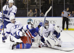 Photo - Tampa Bay Lightning's Tom Pyatt (11) pushes New York Rangers' Brian Boyle (22) into goalie Ben Bishop (30) during the second period of an NHL hockey game, Tuesday, Jan. 14, 2014, in New York. (AP Photo/Frank Franklin II)