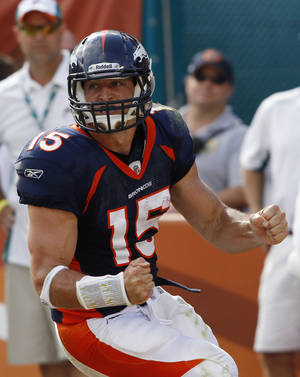 Photo -   Denver Broncos quarterback Tim Tebow celebrates a 2-point conversion during the second half of an NFL football game against the Miami Dolphins, Sunday, Oct. 23, 2011, in Miami. (AP Photo/Hans Deryk)