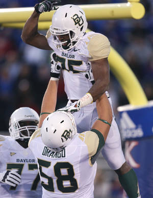 Photo - Baylor Bears running back Lache Seastrunk, top, is hoisted into the air by Spencer Drango (58) after scoring in the first quarter of an NCAA college football game against the Kansas Jayhawks, Saturday, Oct. 26, 2013, in Lawrence, Kan. (AP Photo/Ed Zurga)