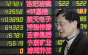 Photo - An investor looks at the stock price monitor at a private securities company on Thursday, March 28, 2013, in Shanghai, China. Renewed jitters about the debt crisis in Europe sent Asian stock markets lower Thursday. (AP Photo/Eugene Hoshiko)