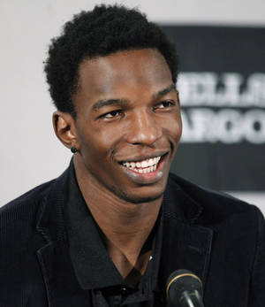 photo - NBA BASKETBALL: Portland Trail Blazers center Hasheem Thabeet talks with reporters during a news conference introducing Thabeet and guard Jonny Flynn on Monday, March 19, 2012, in Portland, Ore. Thabeet and Flynn were acquired, along with a second-round draft pick, from Houston in exchange for veteran Marcus Camby last Thursday at the trade deadline. The Blazers also traded forward Gerald Wallace to the New Jersey Nets for center Mehmet Okur, forward Shawne Williams and a protected first-round pick. The two deals netted the Blazers cap space and added to a stockpile of picks for this June&#039;s NBA draft. (AP Photo/Rick Bowmer) ORG XMIT: ORRB108