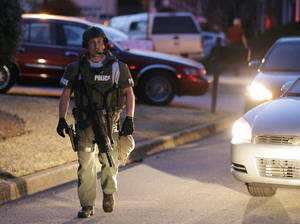 Photo - A police officer leaves the scene after an explosion and gunshots were heard near the scene where a man was holding four firefighters hostage Wednesday, April 10, 2013 in Suwanee, Ga. A police spokesman said the suspect was dead and none of the hostage suffered serious injuries.  (AP Photo/John Bazemore)