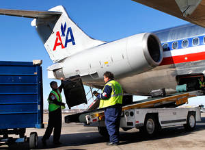 Photo - Baggage handlers load luggage and cargo into an American Airlines aircraft before it pulls away from a gate for a departure flight from Will Rogers World Airport  Tuesday, Nov. 29, 2011. Photo by Jim Beckel, The Oklahoman