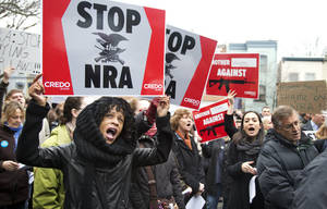 Photo - Tasha Devoe, left, of Lawrence, Mass., joins a march to the National Rifle Association headquarters on Capitol Hill in Washington Monday, Dec. 17, 2012.  Curbing gun violence will be a top priority of President Barack Obama's second term, aides say. but exactly what he'll pursue and how quickly are still evolving.   (AP Photo/Manuel Balce Ceneta)