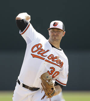 Photo - Baltimore Orioles starting pitcher Chris Tillman throws a warm up pitch in the first inning of a spring exhibition baseball game against the New York Yankees in Sarasota, Fla., Saturday, March 15, 2014. (AP Photo/Carlos Osorio)