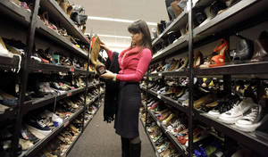 Photo -   In this Thursday, Nov. 1, 2012, photo, a shopper checks a shoe as she walks down an aisle in a Nordstrom rack in Chicago. Nordstrom Inc. is reporting a 15 percent increase in third-quarter net income, fueled by strong demand of men's shoes, men's clothing and children's fashions. The upscale department store chain says Thursday, Nov. 8, 2012, that it earned $146 million, or 71 cents per share for the three-month period ended Oct. 27 (AP Photo/Nam Y. Huh)