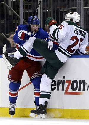 Photo - New York Rangers' Derick Brassard, left, checks Minnesota Wild's Jonas Brodin during the second period of an NHL hockey game, Sunday, Dec. 22, 2013, in New York. (AP Photo/Seth Wenig)