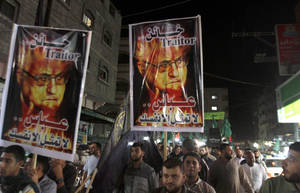 photo -   Palestinians march during a protest against president Mahmoud Abbas in the Jabaliya Refugee Camp, northern Gaza Strip Saturday, Nov. 3, 2012. Gazans protested against Abbas&#039; remarks at an Israeli television that suggested millions of Palestinian refugees and their descendants would not be able to return to the places they fled, or were forced to flee, during the fighting surrounding Israel&#039;s creation in 1948. The posters read: &quot;traitor - you represent nobody but yourself.&quot;(AP Photo/Hatem Moussa)  