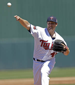 Photo - Minnesota Twins pitcher Phil Hughes warms up in the first inning of an exhibition baseball game against the Boston Red Sox in Fort Myers, Fla., Thursday, March 13, 2014. (AP Photo/Gerald Herbert)