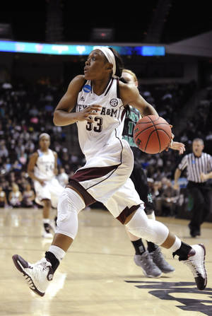 Photo - Texas A&M's Courtney Walker (33) drives to the basket in front of North Dakota's Leah Szabia in the first half of a first-round NCAA women's basketball game Sunday, March 23, 2014, in College Station, Texas. The winner will face James Madison in the second round Tuesday night. (AP Photo/Pat Sullivan)