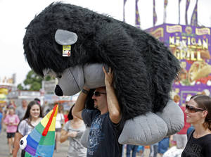 Photo - Dri. Rico Guerra, carries a large stuff gorilla through the Oklahoma State Fair in Oklahoma City, Sunday, Sept. 15, 2013.  His wife, Kari Guerra, is pictured to the right.Photo by Sarah Phipps, The Oklahoman