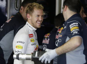 Photo - Red Bull driver Sebastian Vettel of Germany chats with a crew member during the first practice session for the Japanese Formula One Grand Prix at the Suzuka Circuit in Suzuka, Japan, Friday, Oct. 11, 2013. (AP Photo/Greg Baker)