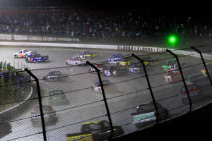 Photo - Drivers head through a turn on the opening lap of the NASCAR Truck Series auto race Wednesday, July 24, 2013, on the dirt at Eldora Speedway in Rossburg, Ohio. (AP Photo/Dayton Daily News, Greg Lynch) LOCAL PRINT OUT AND LOCAL TV OUT (WKEF, WRGT, WDTN)